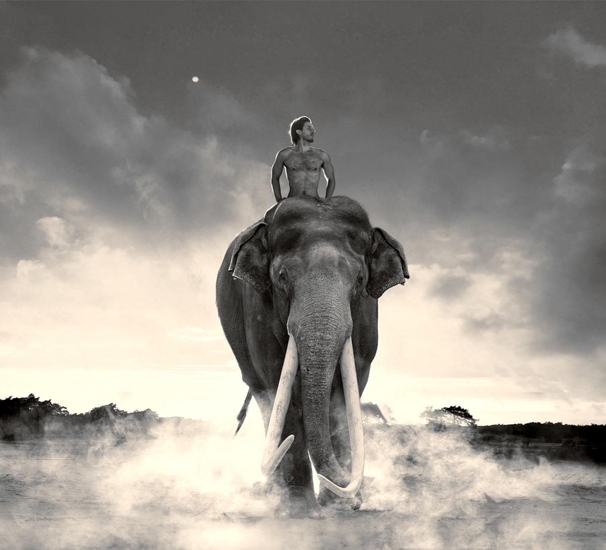 nude man riding on an elephant towards the camera