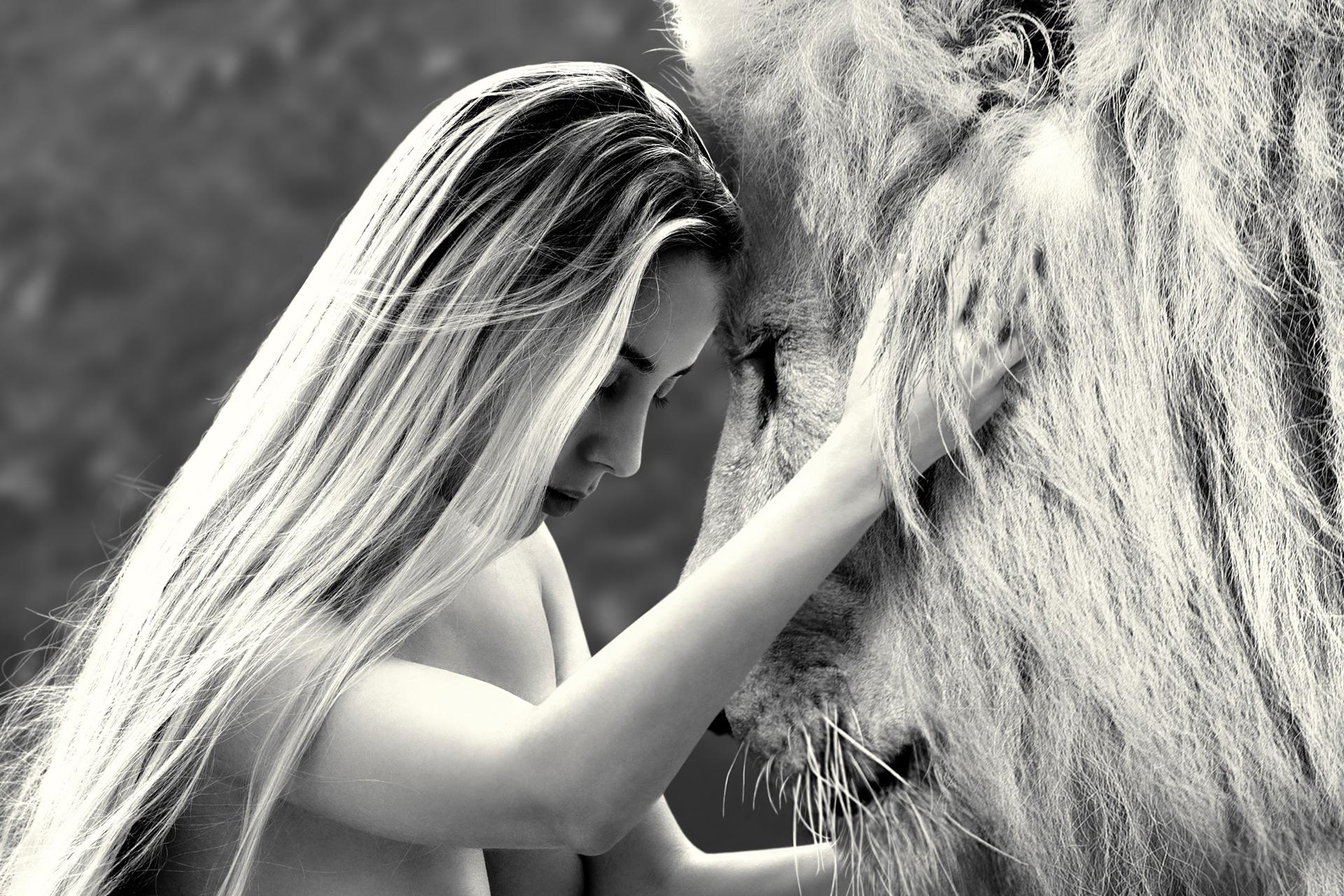 Closeup of a woman hugging a lion